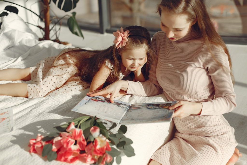 cheerful-mother-and-daughter-reading-book-on-bed-3875332.jpg